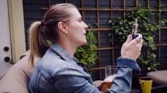 Woman vaping electronic cigarette and holding a glass of beer Stock Footage