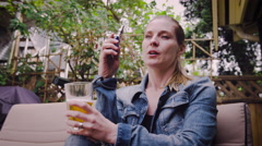 Woman vaping electronic cigarette while having glass of beer Stock Footage