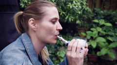 Woman vaping electronic cigarette while having glass of beer - stock footage