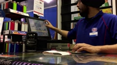 Man buying lottery ticket inside esso gas station convenient store Stock Footage