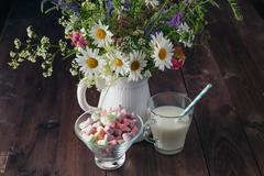 rural breakfast with milk and sweets on wooden table - stock photo