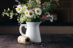 arrangement wildflowers in vase on wooden table - stock photo