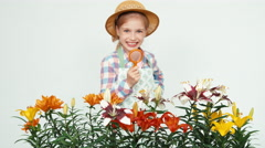 Flower-girl child using magnifier looking at flowers and smiling with teeth Stock Footage