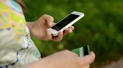 Woman's hands holding credit card and using cell phone, online shopping, outdoor Stock Footage