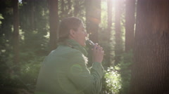 Woman vaping electronic cigarette in forest - stock footage