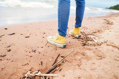 Wooman sneakers on the beach. Sea waves at a sand. Stock Photos
