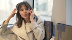 Young, happy woman talking on cellphone during tram ride in city Stock Footage