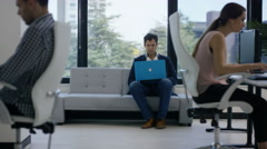 4K Business team working in modern office, focus on man lying down for a rest Stock Footage