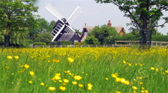 Traditional Windmill and cottage in the English countryside Stock Footage