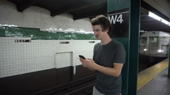 Young man in subway station waiting for train Stock Footage