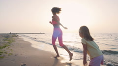 Young mother with her little daugter running on the beach near the water, slowmo - stock footage