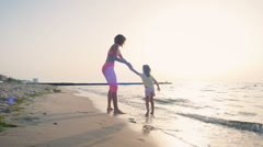 Mother whirling with her little daughter on the beach near the water Stock Footage