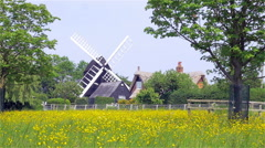 Old English Windmill and thatched cottage in rural setting Stock Footage
