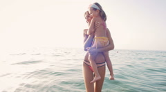 Young mother with her little daugter having fun on the beach near the water Stock Footage