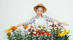 Flower-girl in hat turns near at camera advertises flowers at camera and smiling Stock Footage