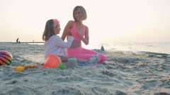 Young mother and her little daughter giving high fives on the beach, slow motion Stock Footage