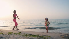 Mother playing with ball with her little daughter on the beach near the water - stock footage