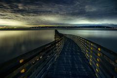 Silhouetted view of winding wooden pier over Puget Sound at dawn, Seattle, Stock Photos