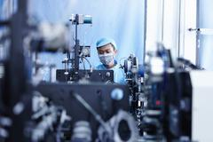 Worker at e-cigarettes battery factory, Guangdong, China - stock photo
