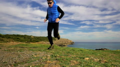 HD pan shot of sport man running towards the camera by sea mountain landscape Stock Footage