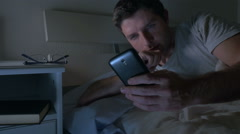 Young attractive man in bed at night networking with Mobile phone Stock Footage