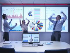 Business people celebrating success in front of graphs on screen - stock photo