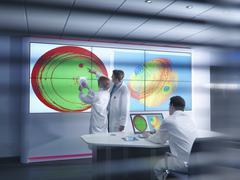Scientists in meeting in front of graphical display of silicon wafer on screens - stock photo