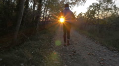 Steadicam of sport man running in countryside off road trail track sunset Stock Footage