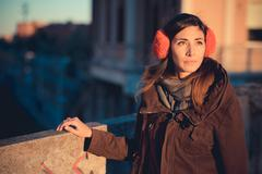 Mid adult woman wearing red ear muffs on city roof top - stock photo