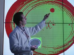 Scientist studying graphical display of silicon wafer on screens - stock photo
