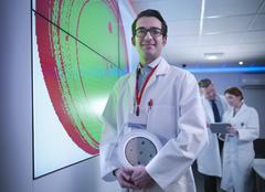 Portrait of scientist in front of graphical display of silicon wafer on screens Stock Photos