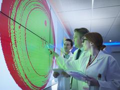 Scientists studying graphical display of silicon wafer on screens - stock photo