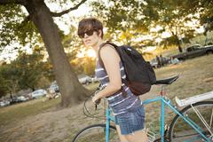 Female cyclist pushing bicycle through park Stock Photos
