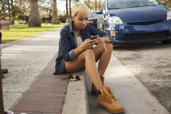 Young woman sitting on kerb, using smartphone - stock photo