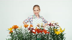 Flower-girl sniffing flowers and smiling at camera on white Stock Footage