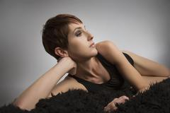 Studio portrait of bored woman lying on black rug - stock photo