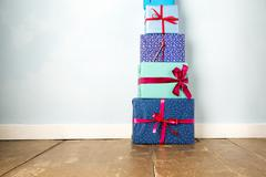 Stack of five wrapped christmas gifts on wooden floor - stock photo
