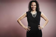 Studio portrait of smiling mature businesswoman with hands on hips - stock photo