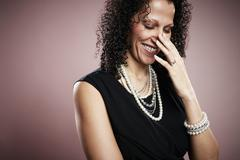 Studio portrait of mature woman with hand on face giggling - stock photo