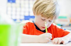Boy writing in exercise book in classroom - stock photo