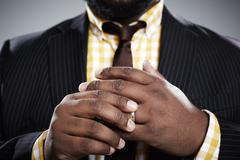 Close up studio portrait of mid adult businessman touching his wedding ring - stock photo