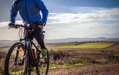 Cropped close up of male mountain biker cycling up dirt track, Cagliari, Stock Photos