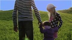 Three children are walking by the green meadow on a blue sky background. Stock Footage