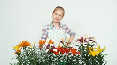 Flower-girl sniffing flowers and smiling at camera Stock Footage