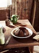 Rustic table with dish of steamed treacle pudding - stock photo