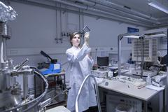 Female scientist examining microscopy slide in lab - stock photo