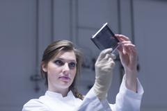 Young female scientist examining microscopy slide in lab - stock photo