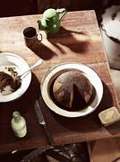 Rustic table with dish of steamed treacle pudding and teapot - stock photo
