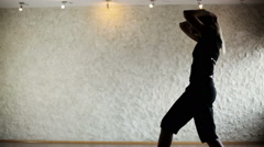 Girl in a dance hall. The dark silhouette of dancing girl in front of light wall Stock Footage