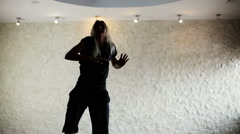 Girl in a dance hall. The dark silhouette of dancing girl in front of light wall Arkistovideo